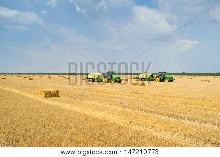 KRASNODAR REGION, RUSSIA - JUL 7, 2015: Tractors makes straw pressed bricks on yellow field after harvest, In 2015 in Krasnodar region have collected record grain harvest - 102 million tons of grain