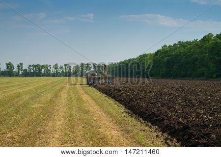 KRASNODAR REGION, RUSSIA - JUL 7, 2015: Modern tractor plow field after harvest, In 2015 in Krasnodar region have collected record grain harvest - 102 million tons of grain