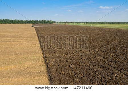 KRASNODAR REGION, RUSSIA - JUL 7, 2015: Modern tractor with plow plowing field after harvest, In 2015 in Krasnodar region have collected record grain harvest - 102 million tons of grain