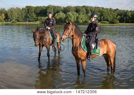 RUSSIA, MOSCOW - JUL 6, 2015: Two horse policemen is standing in Putyaevsky pond at Sokolniki park.