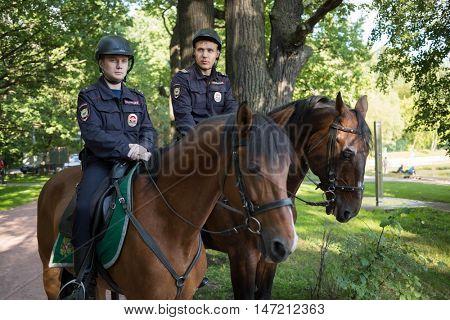 MOSCOW - AUG 6, 2015: Two horse policemen in helmets in green sunny park - police patrols of park Sokolniki