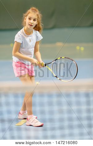 young female tennis player on tennis court holding racquet, in gym, waiting for service