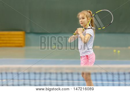 young girl on tennis court holding racquet, in gym, waiting for service