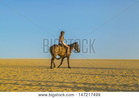 JERICOACOARA, BRAZIL, DECEMBER - 2015 - Young woman riding horse at the beach in Jericoacoara Brazil