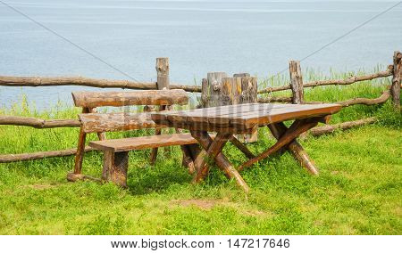 Wooden table and bench on the lawn by the river
