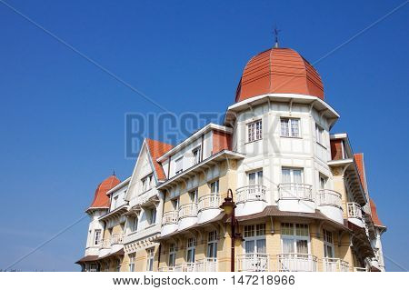 Historical architecture in De Haan Belgium in Belle Epoque style with an interesting red roofed townhouse with corner octagonal turrets and wrought iron balconies against a blue sky