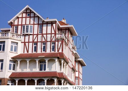 Historical architecture in De Han Belgium in Belle opaque style with an interesting red roofed townhouse against a blue sky