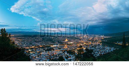 Panorama Of Tbilisi, Georgia. Aerial Cityscape View Of Capital In Evening Illimination, Modern Uptown, Baratashvili Bridge, Sameba Holy Trinity Cathedral. Dramatic Blue Cloudy Sky Of Sunset