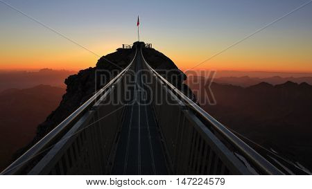 Suspension bridge connecting two mountain peaks. Sunset in the Swiss Alps. Scex Rouge Glacier de Diablerets. Stairway to heaven. Summer scene.
