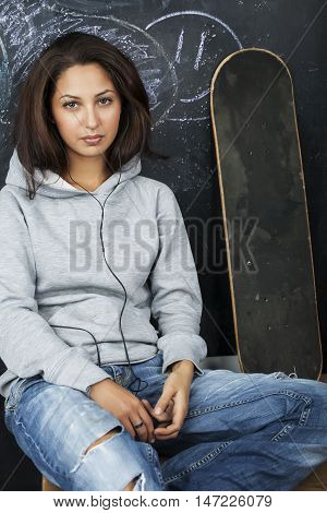 young cute teenage girl in classroom at blackboard seating on table smiling, problem hooligan
