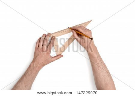 Close-up hands of man while working process with triangle centimeter ruler. Top view composition. Work place of draftsman, architect, constructor.