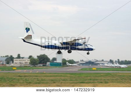Kiev Ukraine - July 31 2012: Antonov An-26 cargo plane is landing in the airport on a cloudy day