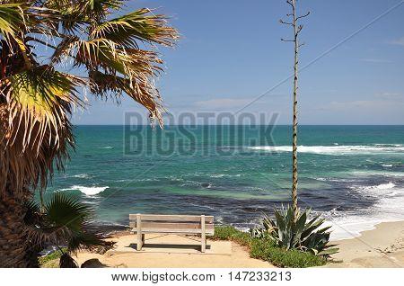 An empty bench sits along the shoreline at a La Jolla beach in San Diego, California.