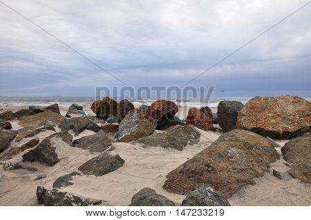 Large rocks are strewn around a Coronado beach in San Diego, California.
