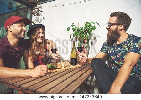 Bearded man with couple drinking wine in summer. Hot red pepper plant and sliced bread are on table.