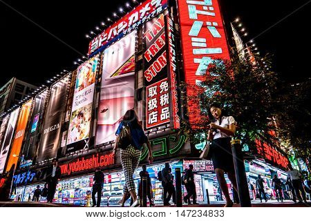Tokyo - May 2016: Night street view with glowing signboards and people, Shinjuku.