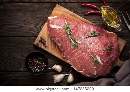 Raw meat. Raw beef tenderloin on a cutting board with rosemary and spices.