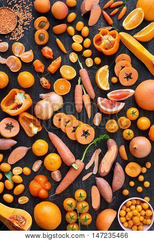Varieties of raw orange hued healthy fruits and vegetables on dark rustic distressed background, vegetarian vegan diet