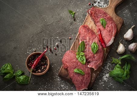 Raw meat. Raw beef chop on a cutting board with basil and spices. Top view with copy space.