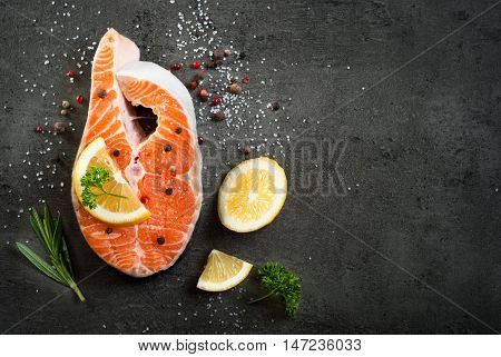 Fresh fish. Salmon. Raw salmon steak with sea salt pepper and herbs. Food background.