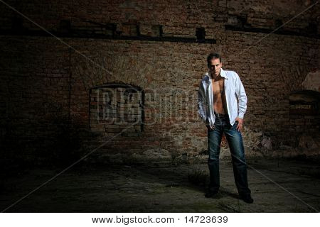 Young muscular sexy male model against retro vintage outdoor background