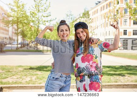 Cute vivacious young women friends standing arm in arm on a hot summer day in an urban street waving at the camera