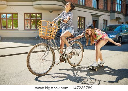 Laughing trendy young woman on a skateboard being towed along an urban street by her friend riding a bicycle