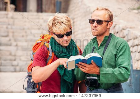 Two tourists try to navigate with guide book