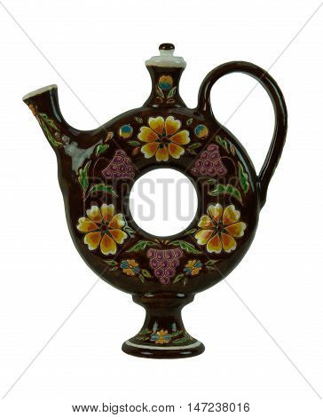Pitcher for beverages in the form of a torus - pottery handmade from clay. Pitcher brown painted with flowers and covered with glaze. Isolated on a white background