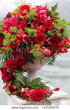 flower arrangement in stone bowl with red roses on bollard
