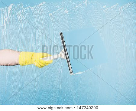 Cleaning concept - hand cleaning glass window pane with detergent and rubber wiper