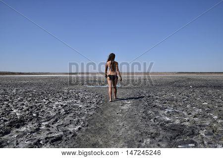 Woman Walking Along The Dry Bottom Of A Salt Lake, Rear View