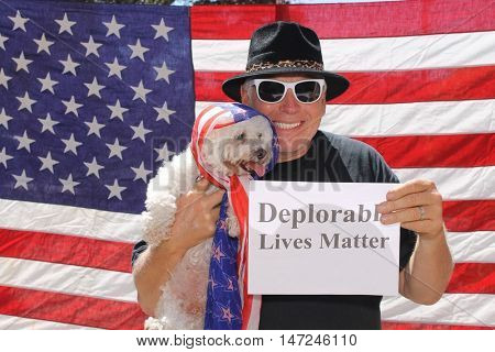 A man and his dog poses in front of am American flag with a Deplorable Lives Matter sign. With his dog.