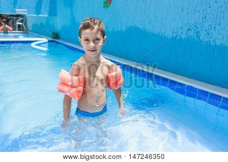 Sweet Little Boy Boy In Swimsuit With Arm Float In The Pool
