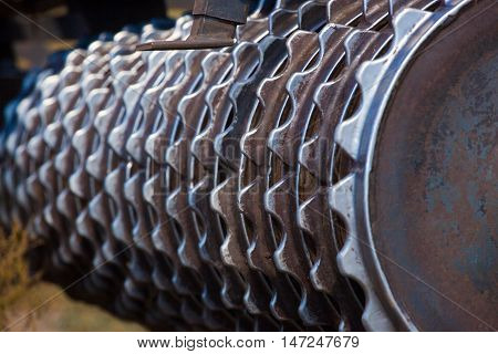 Part of the cultivator steel gear wheels in a row. Close-up. The work of agricultural machinery.