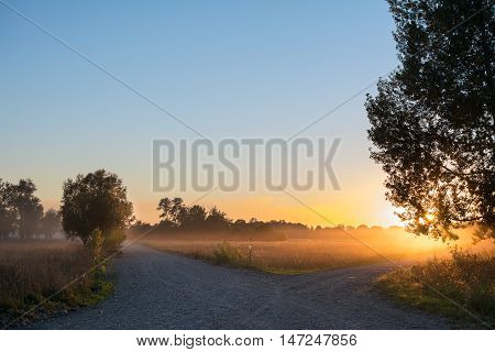 Concept of choice the correct way. Beautiful landscape with sunrise over crossroads spliting in two ways. Rural crossroads on sunset background