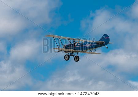 EDEN PRAIRIE, MN - JULY 16, 2016: 1929 Curtis-Wright Travel Air E-4000 biplane flies by at airshow. This biplane is flown by a Minnesota based company for historic flight experiences by passengers.
