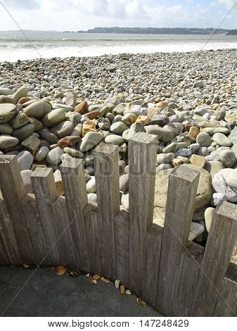 Wooden fence edged Rocky beach seascape photographed at Amroth in Pembrokeshire