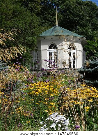 Summerhouse within floral garden and forest backdrop photographed at Colby Woodland Garden near Amroth in Pembrokeshire