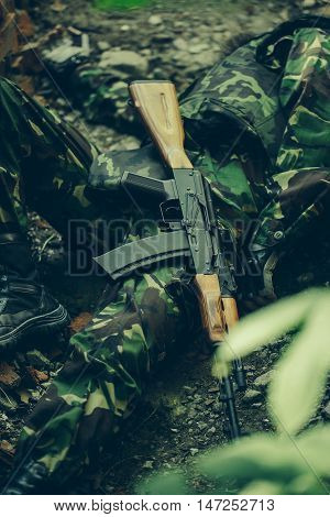Dead body of killed soldier in war dressed in military ammunition laying on ground with rifle outdoor