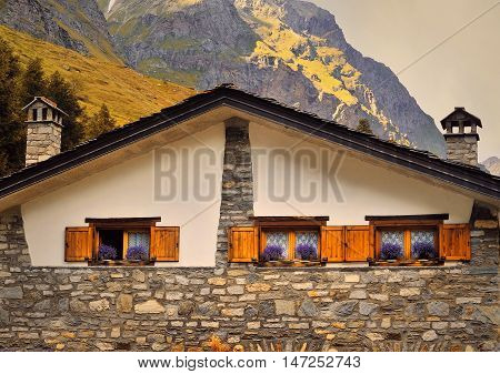 three wooden windows with shutters and violet flowers on alpine architecture facade