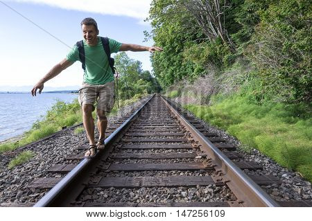 Fun-loving handsome Caucasian man shows his free spirit as he balances on railroad tracks while hiking along beautiful Canadian coast in Surrey British Colombia