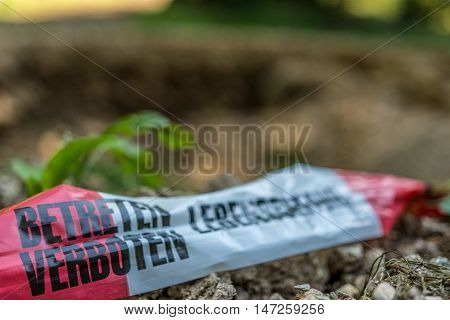 Barrier Tape in front of huge hole in forest