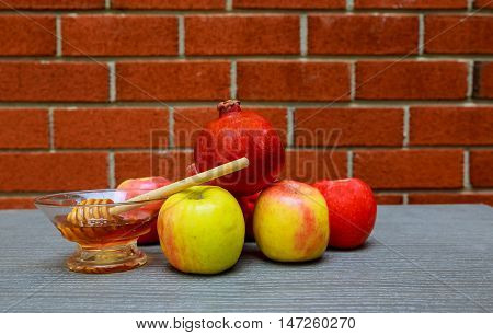 rosh hashanah jewesh holiday honey, apple and pomegranate over wooden table. traditional holiday symbols.