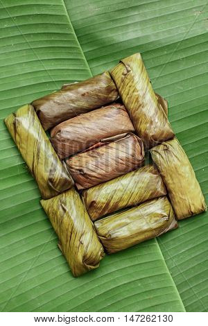 Bananas with Sticky Rice on wooden background. Glutinous rice steamed in banana leaf. Traditional Thai food style Thai name is Khao Tom Mat.