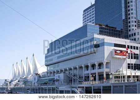 Vancouver, BC - April 20, 2015 - Vancouver BC - a striking sunny view of Canada Place with a blue sky, billboard and Candian flags blowing in the wind. Centerpiece of the Burrard Inlet, a part of Vancouver Harbour
