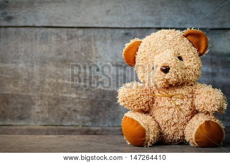 Cute teddy bears sitting on old wood background with copyspace