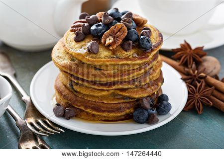 Pumpkin pancakes in high stack with blueberries and syrup served with tea in a bright morning setting