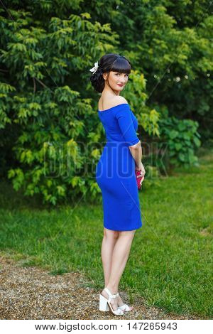 A young attractive woman walking in a park in blue dress.