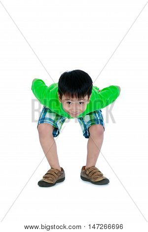 Full body of playful asian child in leather shoes smiling and looking at camera. Stylish boy having fun and standing at studio. Isolated on white background. Studio shot. Positive human emotion.